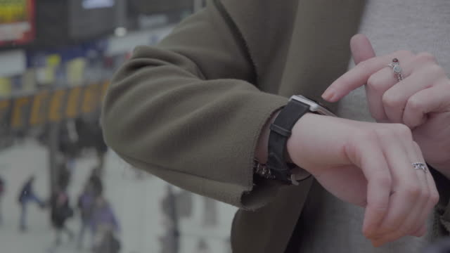 A young woman using a smart watch.