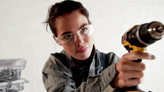 Junge Frau mit elektrischer drill für DIY-PR