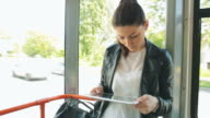 Young woman using digital tablet on tram/train.