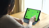 Young woman using digital tablet with a green screen at home