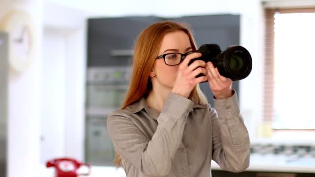 Junge Frau Verwendung von Spiegelreflexkameras, home interior.