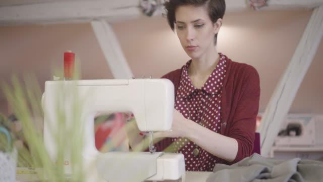 4K: junge Frau mit ihrer Nähmaschine In Werkstatt.