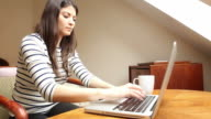 Young woman using laptop and drinking coffee.