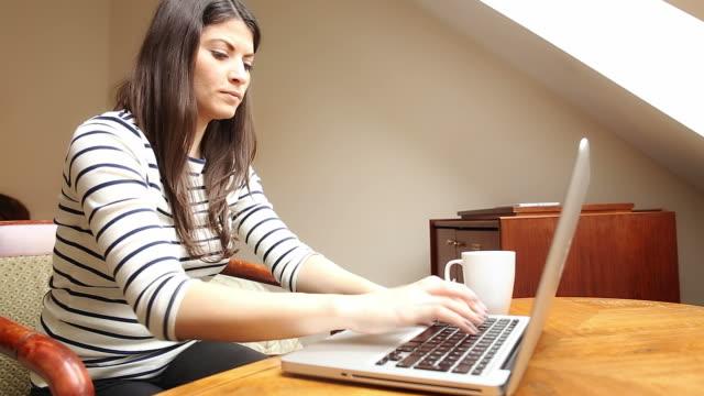 Ung kvinna med laptop och dricka kaffe.