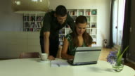 CU, Young woman using laptop, man pointing