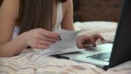 CU TU Young woman using laptop on bed, checking bills / Brooklyn, New York City, New York, USA