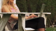 MS ZI ZO WS Young woman using laptop on meadow, Marchin, Belgium