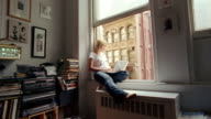 WS, Young woman using laptop, sitting on window sill, New York City, New York, USA