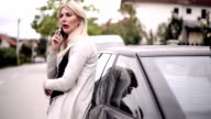 Junge Frau mit Handy neben dem Auto