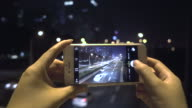 Young woman using smart phone take photo in city night