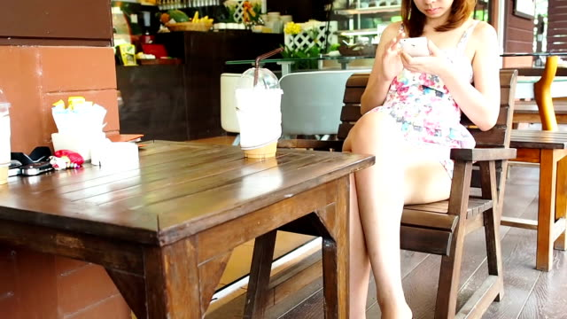 Young woman using smartphone in cafe