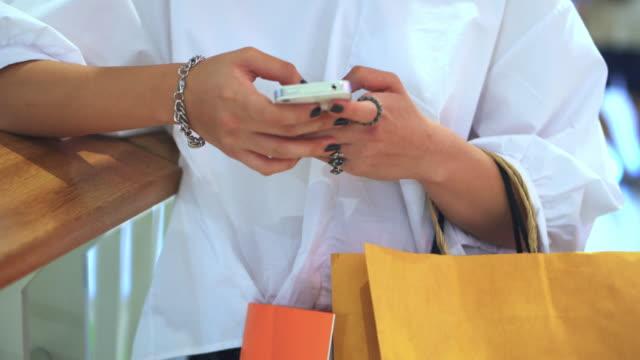 Ung kvinna med smartphone i köpcentrum