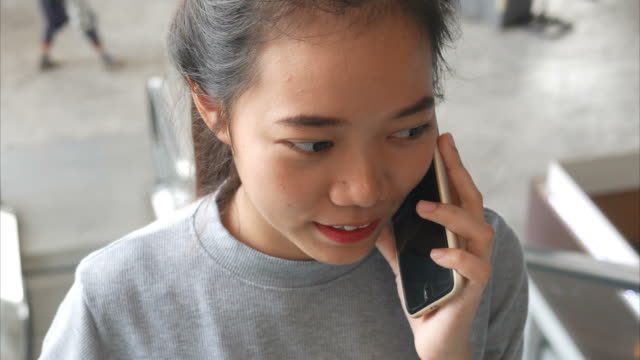 junge Frau mit Smartphone auf Rolltreppe