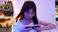 young woman using smartphone with city night background