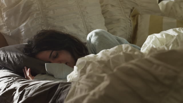 MS Young woman waking up and looking at mobile phone / Provo, Utah, USA