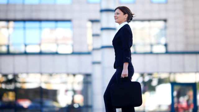 Young  woman walking against the business center.