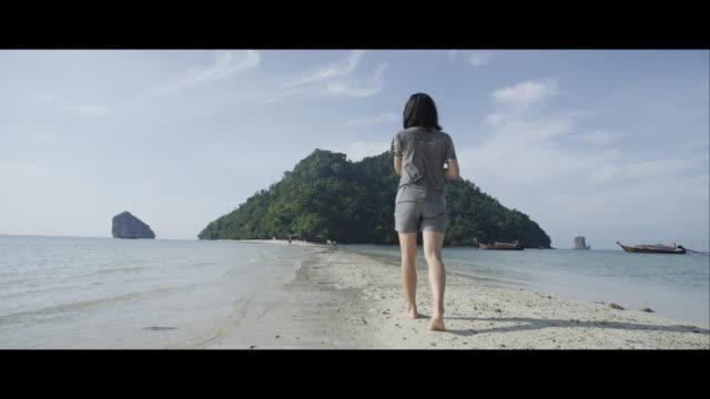 Young Woman Walking Along a Beach