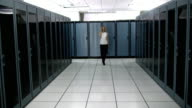 WS DS CU Young woman walking in server room and talking on mobile phone