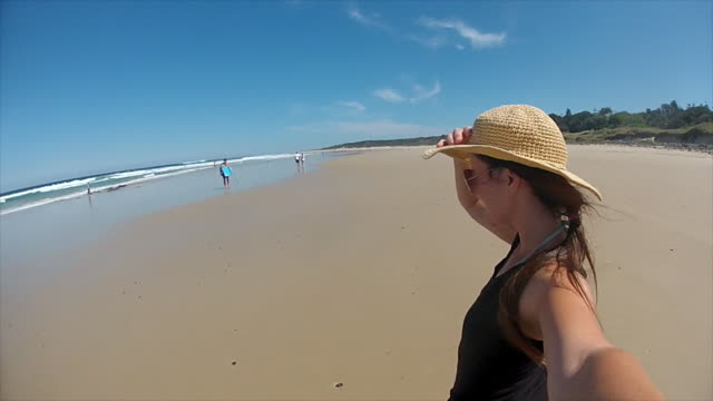 A young woman walking in the beach, at Byron Bay
