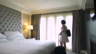 Young woman walking into a hotel room and pulling curtains open