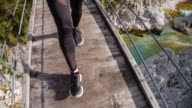 Young woman walking on a wooden suspension bridge over a stream