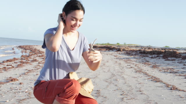 PAN Young woman walking on beach stops to look at a starfish.