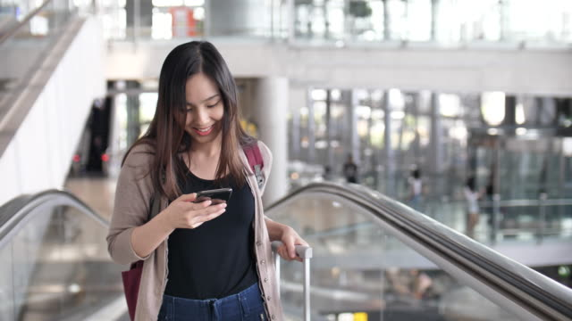 Young woman walking on escalator and using phone, Business Travel