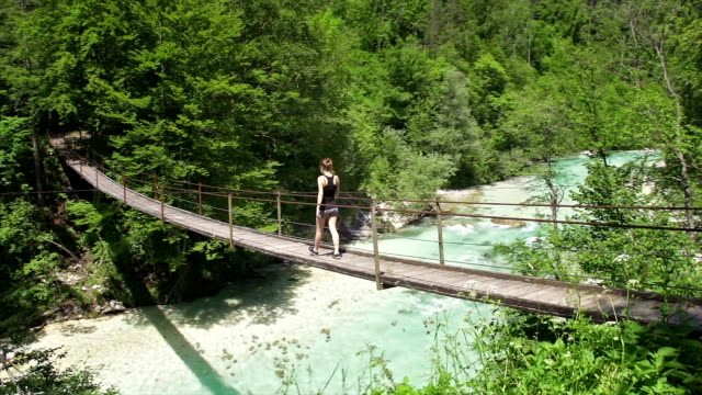Young woman walking over a hanging bridge
