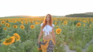 Young woman walking sunflowers field sunset
