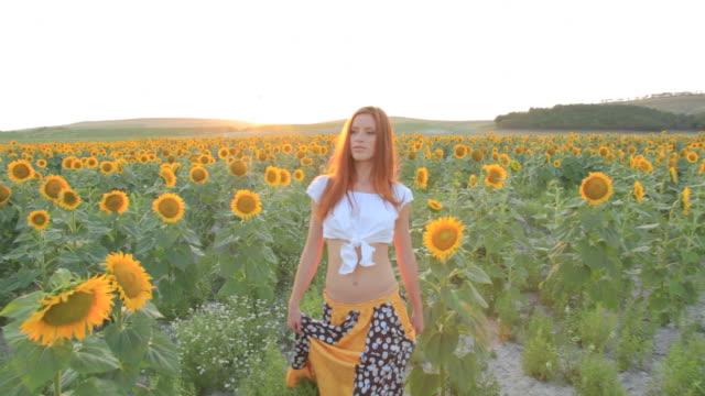 Young woman walking sunflowers field sunset