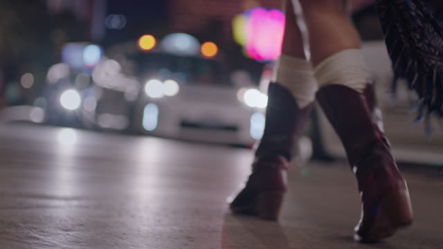 Young woman walks and skips in cowboy boots down Las Vegas strip at night.