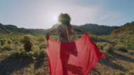 SLO MO. Young woman walks with flowing red scarf casting silhouettes in the Nevada desert.