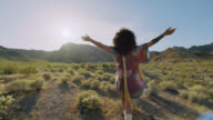 SLO MO. Young woman wandering in the desert throws hands in the air and twirls in the sun.