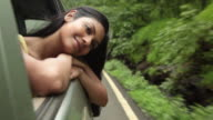 Young woman watching from window of a car, Malshej Ghat, Maharashtra, India
