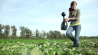Young woman watering crops in field with watering can