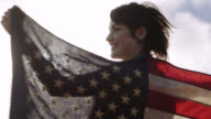 Young woman waves American flag and wraps it around herself in slow motion