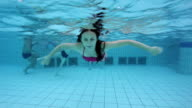 Young woman waving hand underwater