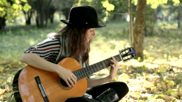 Young woman wearing black hat playing guitar in park, summer.