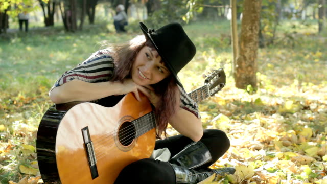 Young woman wearing hat posing in park outdoors, holding guitar.