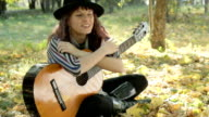 Young woman wearing hat sitting in park outdoors, holding guitar.