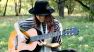 Young woman wearing hat sitting in park outdoors, playing guitar.
