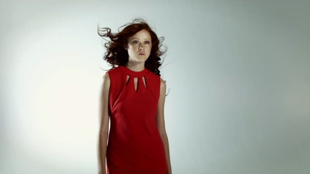 Young woman wearing red dress with windswept hair