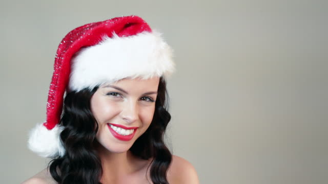 Young woman wearing santa hat and looking up