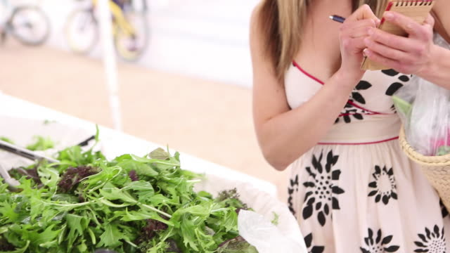 MS Young woman weighing produce at a farmers market / Santa Fe, New Mexico, United States