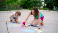 young woman with a child draws a chalk on asphalt, close up