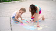 young woman with a child draws a chalk on asphalt on playground in park in summer day, close up