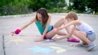young woman with a child draws a chalk on asphalt