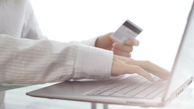 Young woman with a credit card shopping online