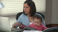MS TU Young woman with baby girl (6-11months) on laps paying bills on line in home office / Richmond, Virginia, USA