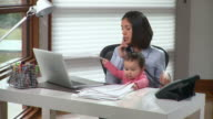 MS Young woman with baby girl (6-11months) on laps talking on phone in home office / Richmond, Virginia, USA